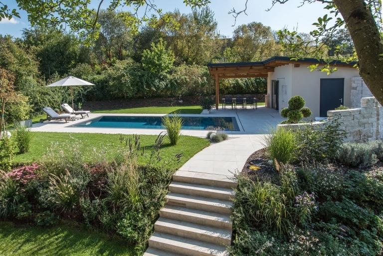 Eine schöne Gartenanlage mit Pool und Poolhaus mit schöner grüner Umgebung Büschen und Sträuchern.