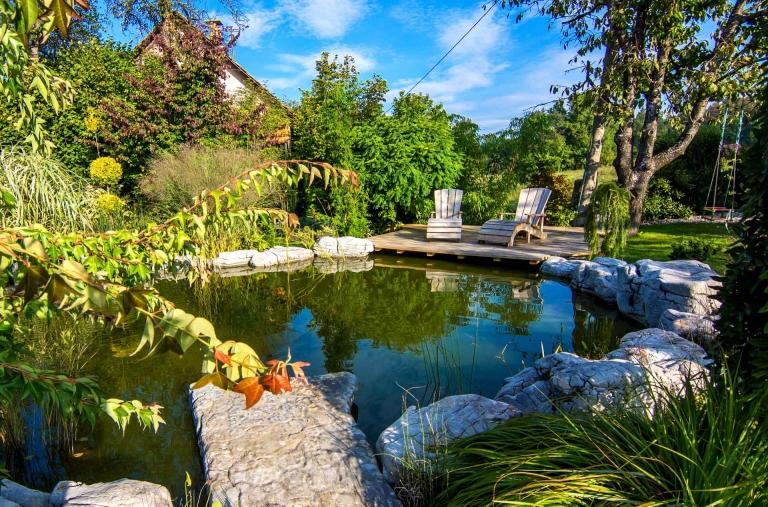 Wunderschöne Teichanlage in einem blühenden Garten mit Holzterrasse