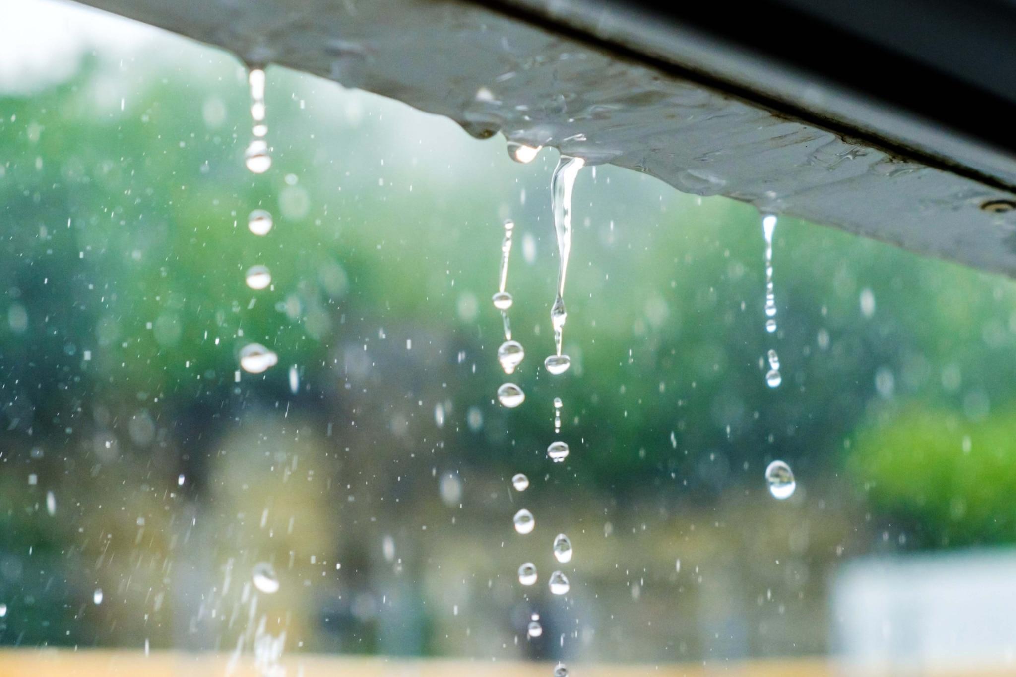 Regentropfen fallen von einer Dachrinnen.