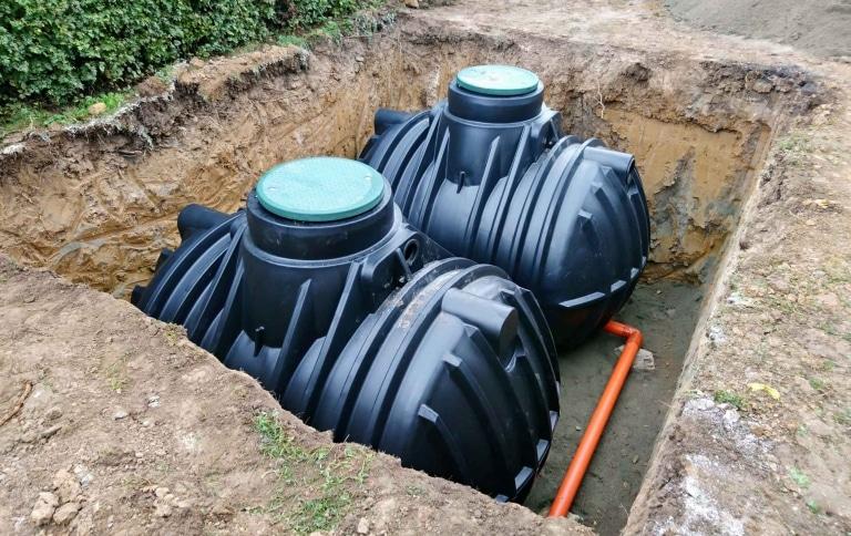 Zwei schwarze Regenwassertanks in einer ausgehobenen Erdgrube mit einem Ableitungsrohr