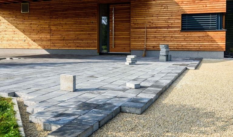 Graue Pflastersteinen werden zum Terrassenbau vor einem Haus mit Holzfassade verlegt.
