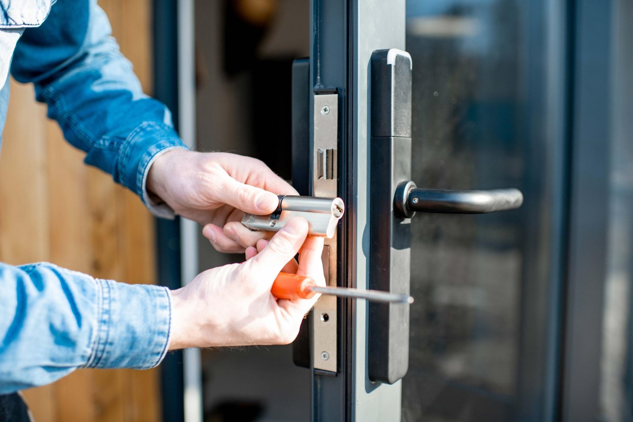Ein silbriges Zylinderschloss wird bei einer Außentür installiert.