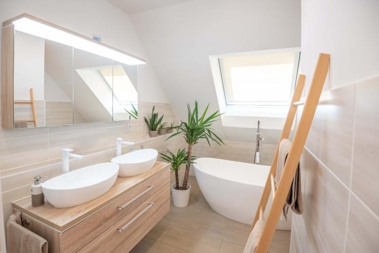 Ein sehr helles Badezimmer mit modernem Doppelwaschbecken und Badewann mit hellen Holzmöbeln und cremefarbenen Fliesen