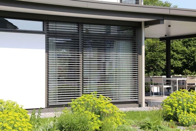 Beschattung mit Jalousie in ansprechendem grauen Farbton auf großflächigen Fenstern.
