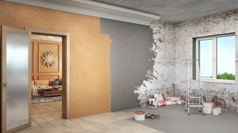Ein halb renvoierter Raum mit teils bereits aufgetragener neuer Farbe und teils roher Hausinnenwand mit Renovierungsmaterial und Werkzeug.