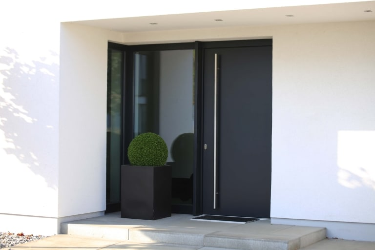 Eine moderne Eingangstür in eleganter Anthrazit-Farbe mit einer langen vertikalen Griffstange aus Edelstahl.