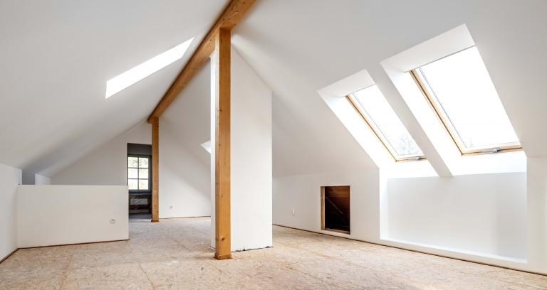 Ein ausgebauter Dachboden mit großzügigen Dachfenstern und schön geweißten Wänden und Decken zusammen mit dem schönen Dachgiebel aus Holz.