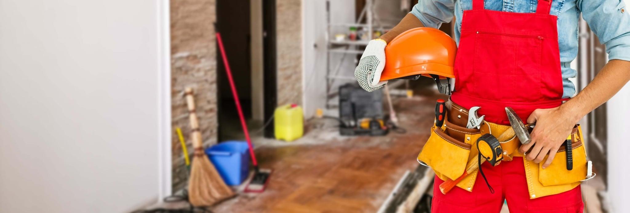Handwerker beim Bauen, Sanieren und Renovieren mit Werkzeugen im HIntergrund