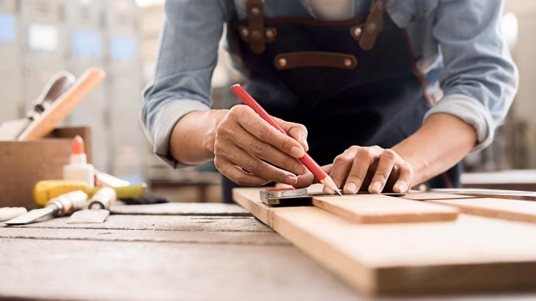 Ein Heimwerker macht eine Markierung auf einem Stück Holz mit einem Zimmermannsbleistift in einer Werkstatt