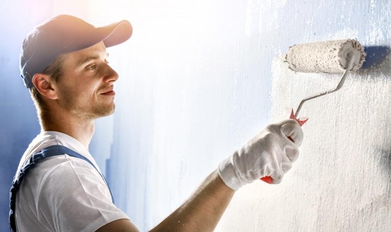 Ein Maler trägt mit einem Farbroller weiße Farbe auf eine blaufärbige Wand auf.