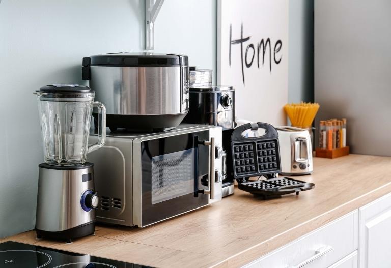 Mikrowelle, Mixer, Waffeleisen und weitere Küchengeräte mit schönen Metall-Gehäusen af einer hölzernen Arbeitsplatte in einer Küche