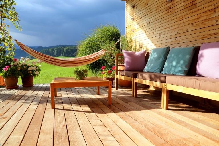 Eine Terrasse aus hellen Holzdielen mit Holzmöbeln einer gemütlichen Hängematte mit einer schönen Hügellandschaft im Hintergrund.