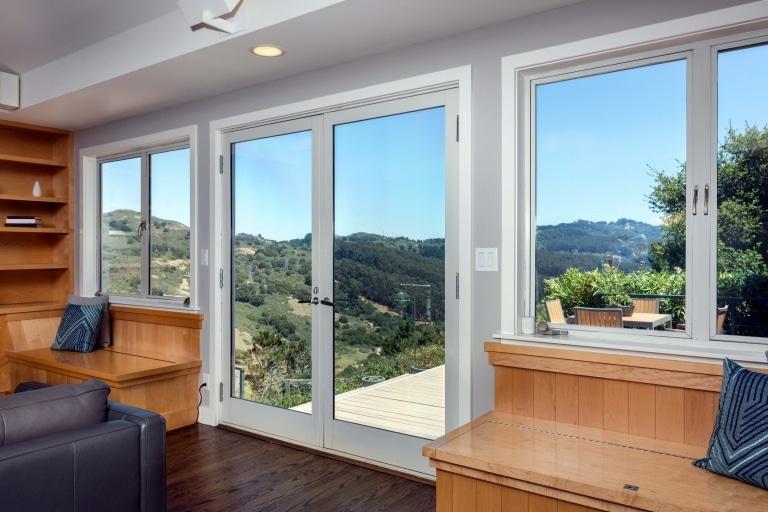 Blick auf eine bergige Landschaft aus einem Wohnzimmer mit großen Fenstern und schönen Holzmöbeln
