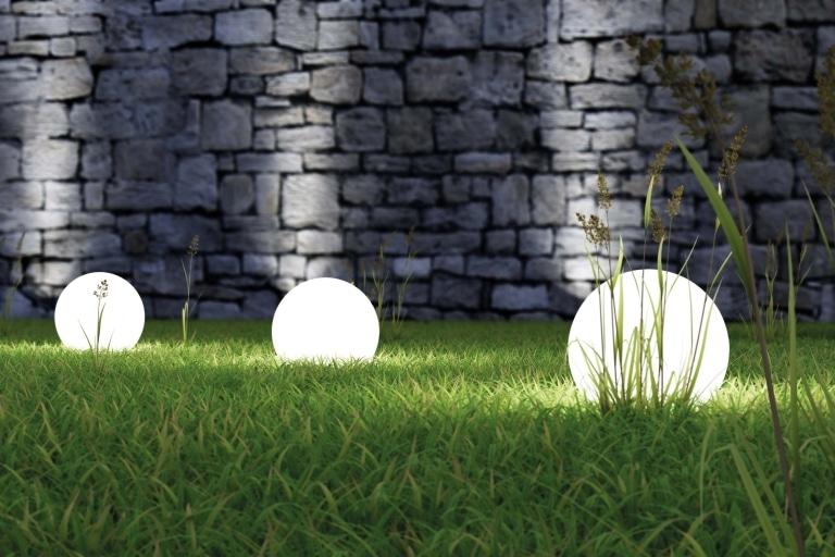 Ein Gartenbereich mit runden Standleuchten die Wiese und eine Mauer in der Nacht erleuchten.