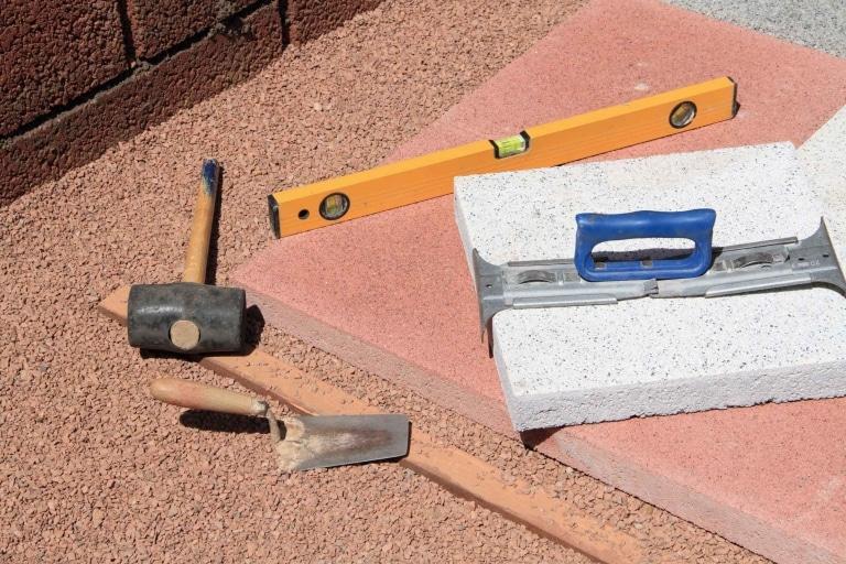 Verschiedene Zubehörteile für den Terrassenbau, ein Gummihammer, ein Plattenheber aus Metall und eine Wasserwaage werden zur genauen Verlegung eines weißen Pflastersteines verwendet.