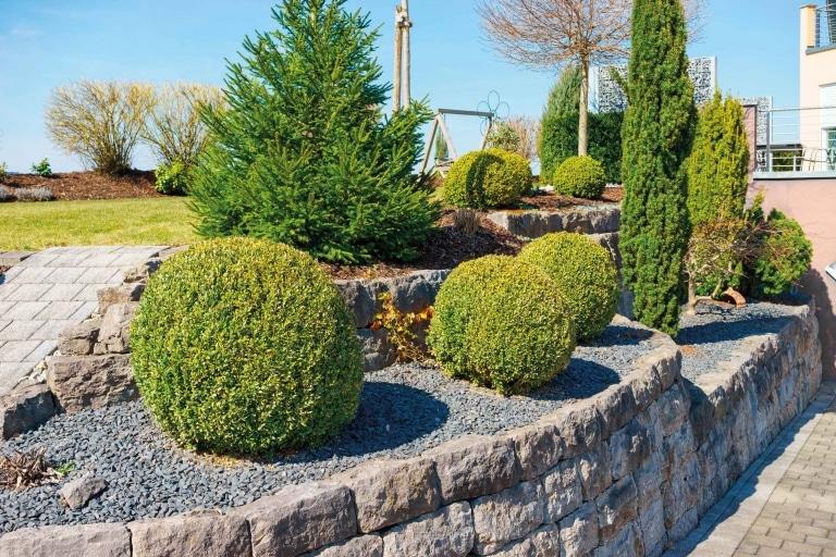 Vorgarten mit Hochbeet aus Boschüngssteinen und schön gestalteten Büschen.
