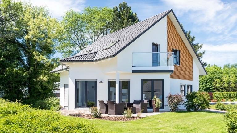 Ein modernes Einfamlienhaus mit dezenten schrägen Elementen im Grundriss, großen Fensterflächen, Terrasse und Grünanlage