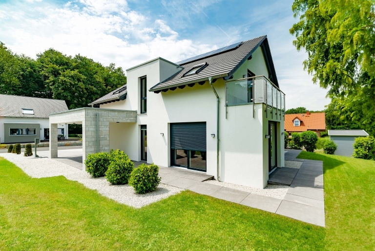 Einfamilienhaus mit modernen Designelementen wie einem Vorbau aus Steinen, ein Flachdachelement und Satteldach, großen Fenstern, einem Balkon mit Edelstahl und Glasgeländer