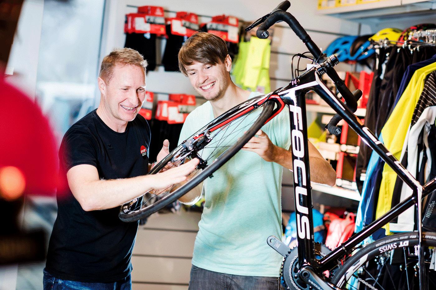 Sportfachberater zeigt jungen Mann die Speichen eines Fahrrades